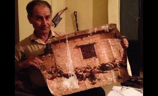 Overlevende Hamad Chamas der holder op et foto over kroppe han gemte sig under i 2 dage i flytningelejren i 1982.