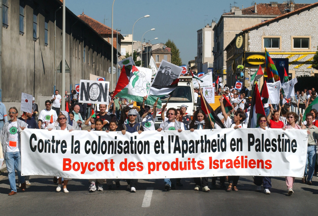 "Demonstrators holding a banner reading ""Against colonization and apartheid in Palestine, Boycott of Israeli products,"" march through the northern district of Marseille, southern France, during an international demonstration in support of the Palestinians Saturday, Sept. 28, 2002. Demonstrators, some coming from Spain and Italy, wished to express solidarity with the Palestinian people on the second anniversary of a renewed uprising against Israel.(AP Photo/Claude Paris)"